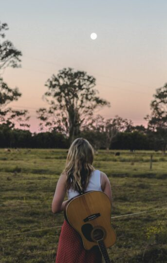 Woman with guitar in field at dusk